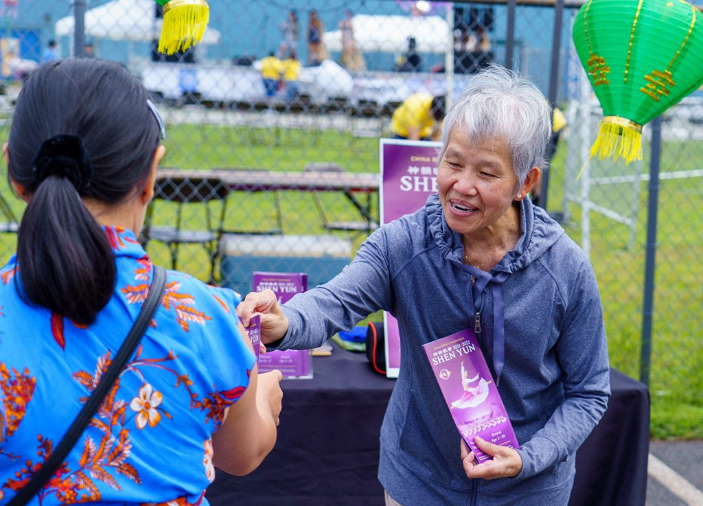 A volunteer introduces Shen Yun to a passersby at the Mid-Autumn Lantern festival in Randolph, MA.
